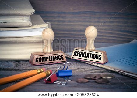 Compliance and Regulations concept. Rubber Stamp on desk in the Office. Business and work background.