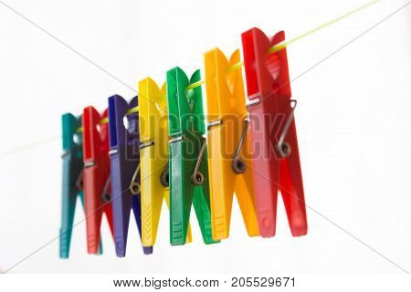 Colorful clothespins hanging on a clothesline. The background is white.