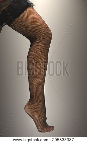 Sexy female legs in fishnet pantyhose stockings standing on toe cap isolated.