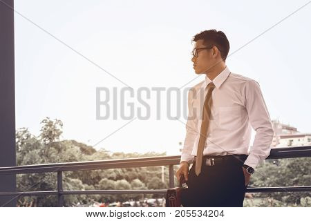 Worried businessman standing at office about work and thinking for future.