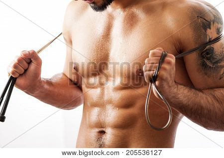 Muscular sexy fitness model posing shirtless with jumping rope on shoulders. Studio shot of Athletic young man with tattooed torso on white background.