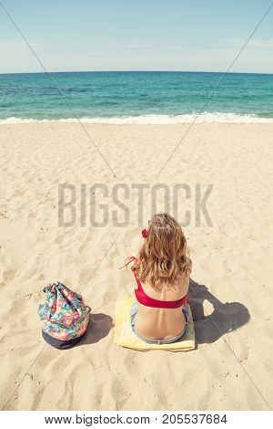 Young woman sitting on a sandy beach and looking at the sea / ocean.