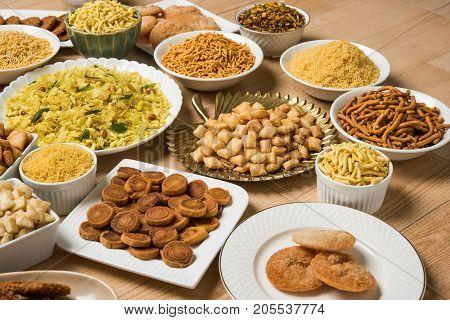 stock photo of  Diwali food or Diwali snacks or Diwali sweets like anarsa, bakarvadi, chakli, sev, bhujiya, shankar pale and chivda or chiwada, karanji, favourite indian diwali recipe, selective focus