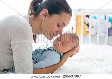 Happy Mother, Talking To Her Newborn Son, Stroking And Kissing Him