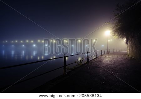 The river Loire and Cessart bridge at night in a mist seen from Quai de la Marine riverbank in Saumur France.