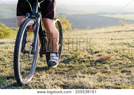 Closeup of cyclist man legs and hands riding mountain bike on outdoor trail in nature. Spotr and travel concept