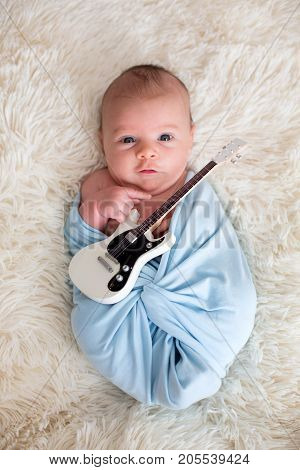Newborn Baby Boy, Holding A Little Guitarand Smiling