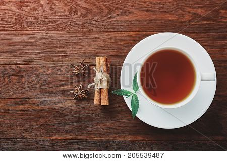 White porcelain cup of tea with cinnamon sticks, lemon, mint leaves and tea strainer on wooden rustic table.