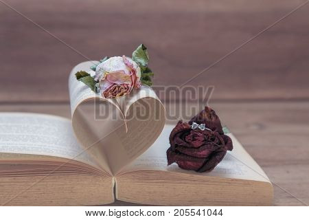 Marriage proposal love concept Dried red roses with rings making a proposal to Dried pink rose on old Heart shaped book pink tones.