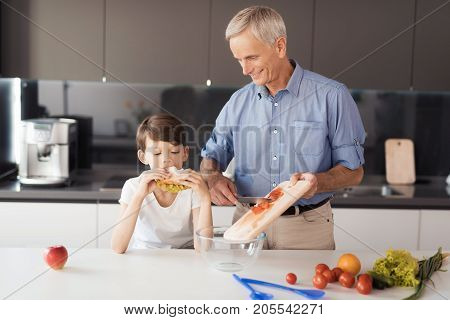 An old man in a blue shirt prepares a salad for dinner on the day of the lag. His grandson stands next to him and eats a sandwich with slate leaves