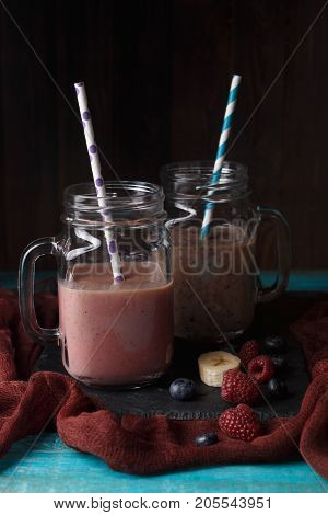 Image of two jars with smoothies on table with banana, blueberries, raspberries on wooden background