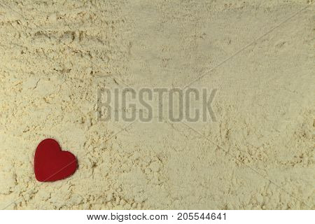 Red heart on white sand/ This is red heart  on white background.