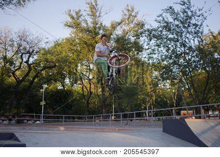 BMX rider training and do tricks in street plaza, bicyxle stunt rider in cocncrete skatepark