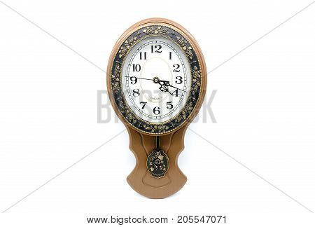 Old brown clock with pendulum and dial against white background