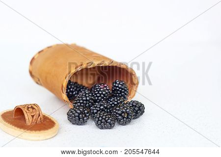 Blackberries in birch bark basket on a white background
