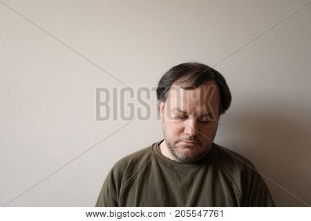 depressed man in his forties leaning against wall with copy space. depression or midlife crisis concept.