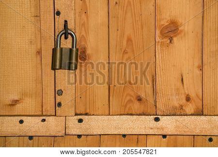 Closeup of the padlock on a wooden rustic door