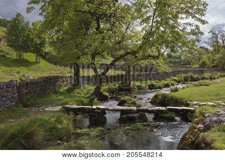 Old stone footbridge crossing the Malham Beck at Malham Cove Yorkshire Dales National Park England.