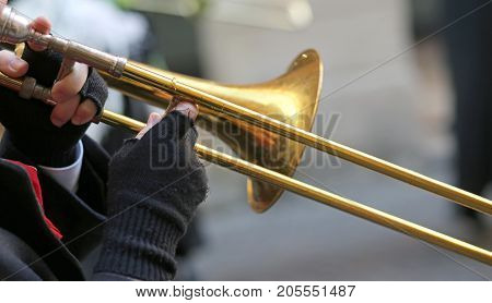 Hand Of Elderly Man With Gloves Playing The Trumpet