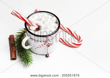Hot chocolate with marshmallow on white wooden table. Top view with copy space. Vintage mug of winter cocoa with cinnamon stick. Christmas cozy home concept