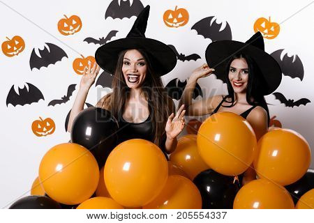 Two sexy witches posing with black and orange ballons in their hands. They are dressed in witches' hats and black dresses. Models are smiling