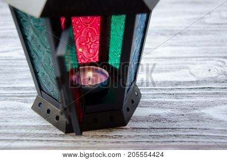 Beautiful lantern with a candle burning inside (on a gray wooden background) selective focus on the candle