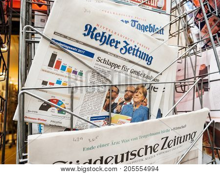PARIS FRANCE - SEP 25 2017: Man buying latest German Kehler Zeitung newspaper with portrait of Angela Merkel after election in Germany for the Chancellor of Germany the head of the federal government