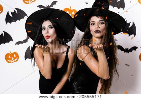 Two sexy models posing against white background with paper bats, making confetti with a hand in the camera. They are dressed in black tight dresses and witches' hats