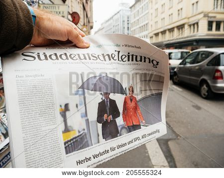 PARIS FRANCE - SEP 25 2017: Man buying latest suddeutsche zeitung newspaper with portrait of Angela Merkel with her husband Joachim Sauer after winning the election in Germany for the Chancellor of Germany the head of the federal government