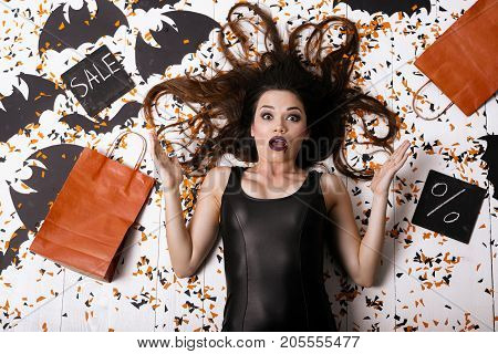 Crazy discount for Halloween. A sexy model in a black tight dress lies on the floor surrounded by confetti and paper bats. It depicts shock