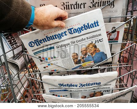 PARIS FRANCE - SEP 25 2017: Man buying latest german offenburger tageblatt newspaper with portrait of Angela Merkel after winning election in Germany for the Chancellor of Germany the head of the federal government