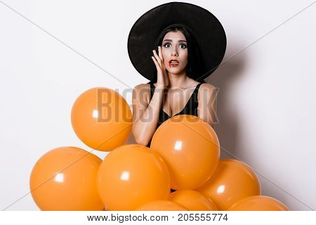The sexy model in black and lapatya and witch hat is on a white background and holds orange ballons. It depicts anxiety