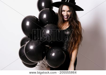 A model poses on a white background with black balloons and a tight black dress and a witch's dress. She cheerfully laughs