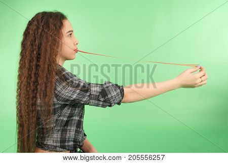 Young girl stretching from chewing gum which he carries in his mouth isolated on green background