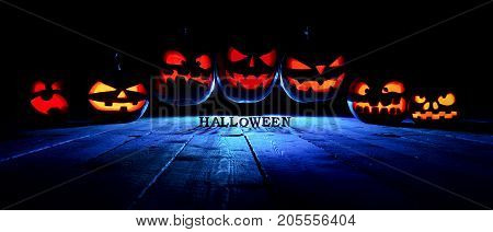 The Concept Of Halloween. A Lot Of Glowing Fiery Light Angry Scary Pumpkins Flying Through The Air.