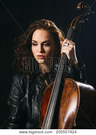 Photo of a beautiful woman holding her old cello.