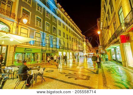Lisbon, Portugal - August 24, 2017: people walk in pedestrian and popular Rua Augusta between cafes and shops in Baixa, downtown Lisbon, by night. The Triumphal Arch on background.