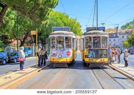 Lisbon, Portugal - August 27, 2017: two yellow historic Trams 28 at Estrela Basilica terminal and people waiting to climb the icon of Portuguese capital. Urban views. Prazeres and Carreira directions.