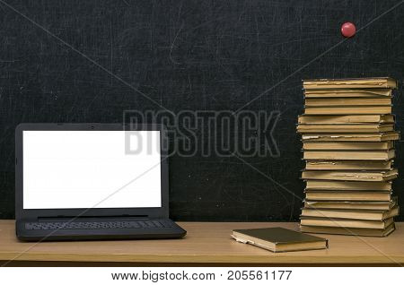 Teacher or student desk table. Education background. Education mockup concept. Laptop with blank screen stacked books and textbook on blackboard (chalkboard) background.