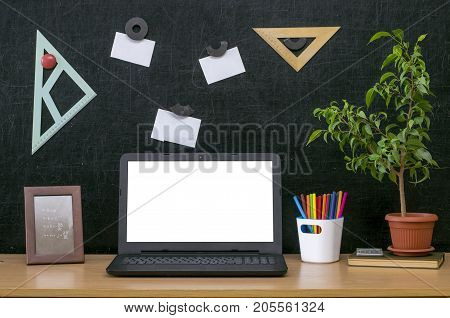 Teacher or student desk table. Education background. Education mockup concept. Laptop with blank screen green plant tree book colour pencils photo frame and note page stick on blackboard.