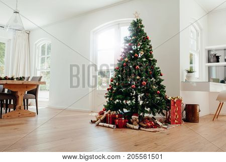 Interior of living room decorated for Christmas. Decorated Christmas tree with gifts all around it.
