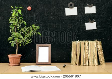 Teacher or student desk table. Education background. Education concept. Stacked books copybook book green plant tree photo frame and note paper on blackboard background.