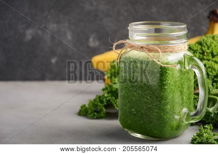 Fresh green smoothie with kale and banana, selective focus, copy space.