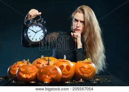 Halloween time. Sullen woman with Halloween pumpkins holding big alarm clock