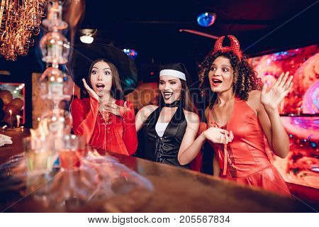 Flaming cocktail on the bar. A girl in a nun costume, a girl in a demon costume and a girl in a witch costume watch a flaming cocktail. They are delighted
