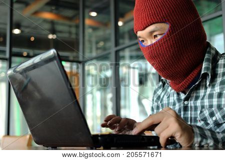 Masked hacker wearing a balaclava looking a laptop and stealing important information data. Network security and privacy crime concept.