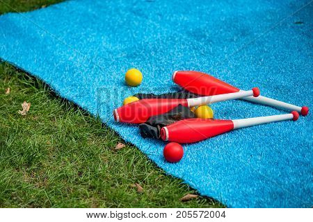 Close up image of colorful juggling equipment lying on blue mat outside