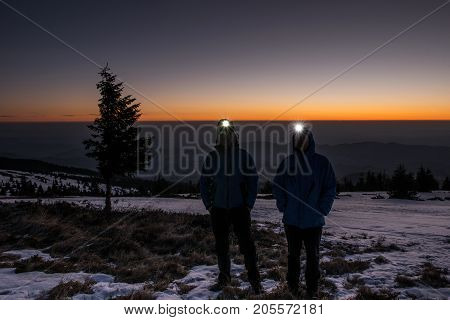 Two trekkers posing during a winter sunrise in the mountains with headlamps turned on