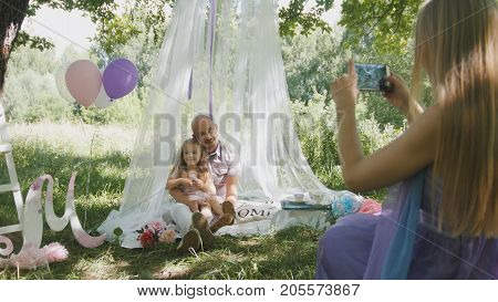 Family's picnic in park - mother take a photo on a mobile phone - little daughter and husband