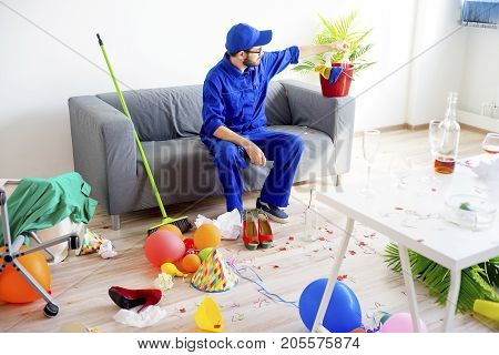 A janitor is cleaning a mess after a party